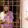 India: Hindu woman behind the gate of her front door